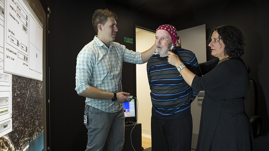 Researchers Alex Smith (L) and Dr Deborah Anthrop (R) work with Parkinson's disease sufferer Ken Hood (middle).