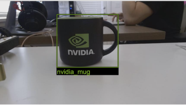A photograph of an NVIDIA-branded coffee mug placed on a desk with a person working on the background. A bounding box is overlaid around the mug. Underneath the box is the legend 'nvidia_mug'.