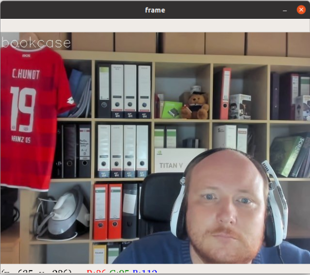 An image of the author sitting in front of his bookcase recorded by a webcam and subsequently being fed to a ResNet50 model that assigns the correct label: bookcase.